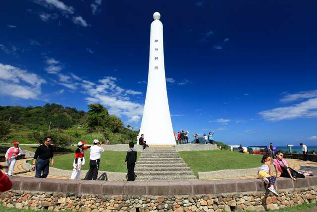 Visitors take a photo of the Tropic of Cancer under the plan marked Monument